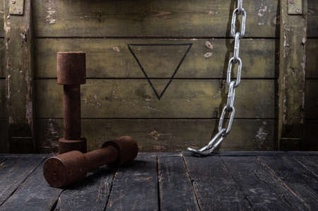 Old rusty dumbbells and chain. Dark room with dumbbells. Front view.
