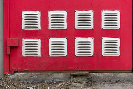 Ventilation hood. White squares on a red background. Red wall. Duplicate objects. Daylight.
