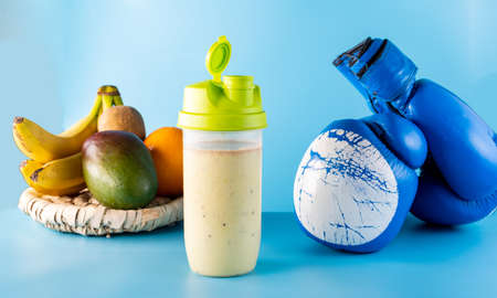 Vitamin protein sports nutrition. Multivitamin food from fruits. Milk cocktail and boxing gloves. Blue background.