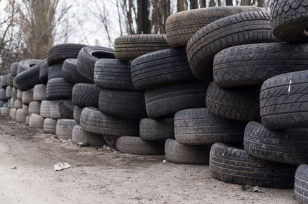 A wall made of old wheels. Wall made of old car tires. Fencing from wheels.