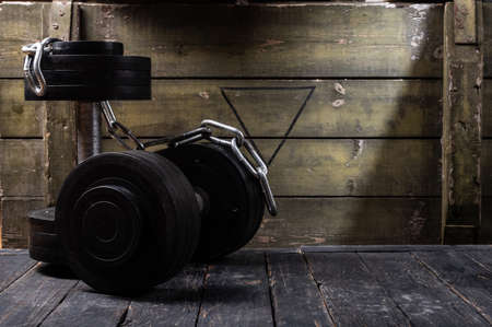 Dumbbells for sports. Dumbbells with black discs. Dumbbells and chain. Dumbbells in the basement.