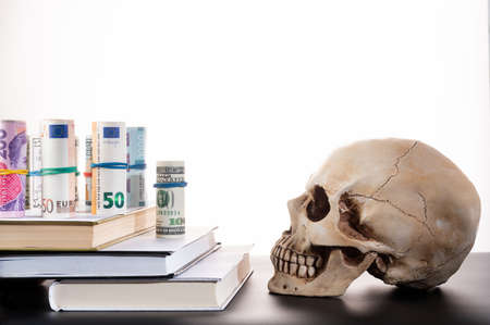 Money on the steps. Money on books. Money of different currencies and a skull.