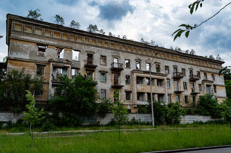 An old abandoned house. Emergency high-rise building. House without tenants. The house is overgrown with trees.