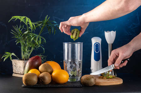 Slicing kiwi for smoothies. Kiwi slices and blender. Throw fruit into blender. Kiwi slices and a knife in hand. Фото со стока