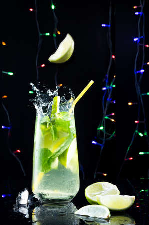 Cocktail and Christmas lights. Cocktail on the table on a background of colored lights. Mahito with splashes and levitation.