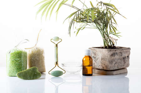 Roller for smoothing the skin. Cosmetic bath salt. Skin and body care. Massage oil. Pot on the table. Фото со стока
