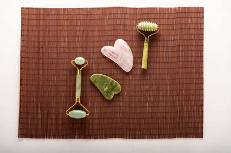 Rollers and stones for leather. Natural stones for smoothing the skin. Cosmetic tools on a bamboo mat. Top view.
