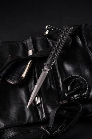 Mens accessories in black. Black style. Large folding knife, watch, pocket torch and wallet. Vertical frame. Фото со стока