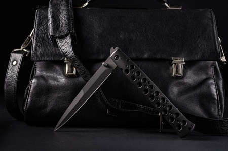 Large folding knife on the background of a leather briefcase. Bent knife and leather briefcase.