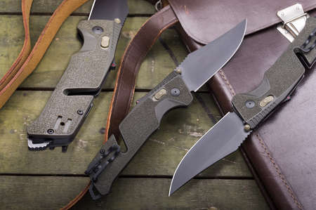 The knife is shown in three angles. Folding military knife. Knife and military tablet. Top view. Фото со стока