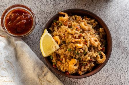 Serve paella with shrimp and lemon. Serving paella with lemon and sauce. Фото со стока