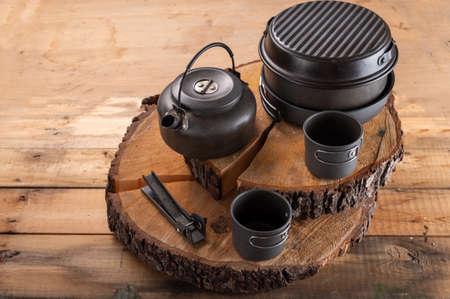 Tourist tableware stumps. Aluminum tableware for tourism. Pots and kettle on stumps.