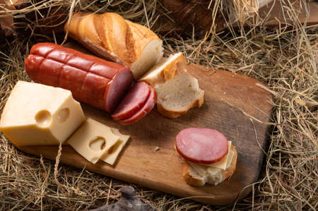 Meat and cheese cuts. Homemade cheese and meat. Rustic style. Variety of cheese and meats on a cutting board. Top. Фото со стока