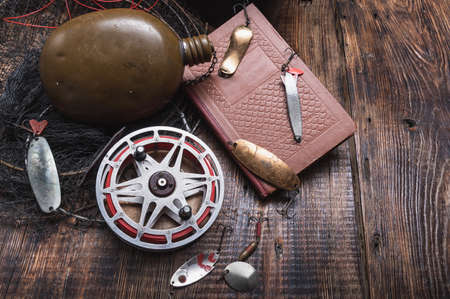 Old Soviet fish bait. Fishing lures and a book. Instructions for fishermen. Iron fishing lures with hooks.
