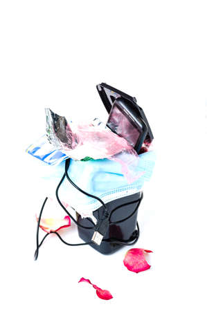 Garbage in a trash can top view. Medical mask, smartphone and wires in the trash. Rubbish on a white background. Фото со стока