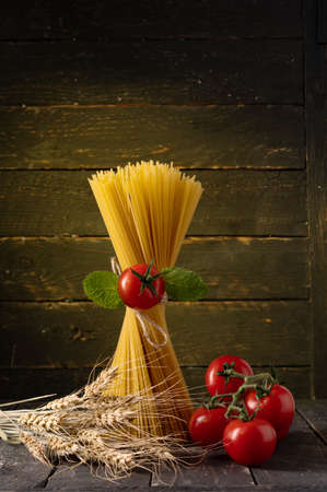 Spaghetti and tomatoes. Spaghetti and spikelets of wheat. Pasta and a branch of tomatoes.