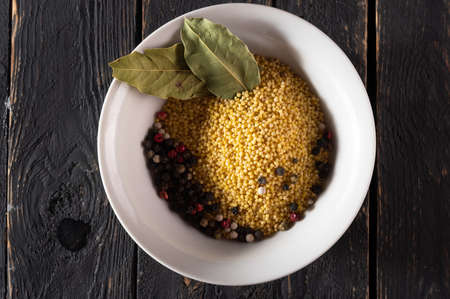 Millet and spices. Millet and bay leaves. Millet for cooking porridge. Millet in a plate. View from above. Фото со стока