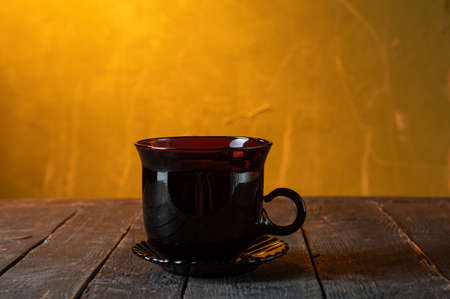 Glass black mug. A mug for tea on a wooden table. Yellow background.