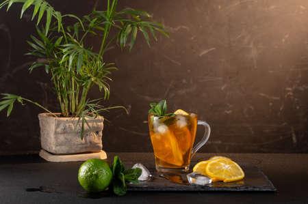 Iced tea with lemon and mint. Tea with ice cubes and lemon wedges. Refreshing iced tea.
