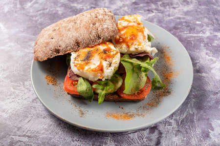 Poached egg sandwich. The eggs are sprinkled with a variety of spices. Sandwich on a plate. Фото со стока