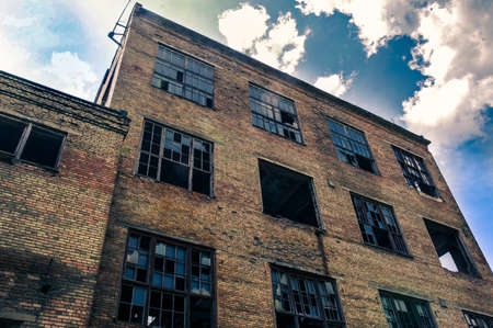 An old abandoned house. Factory with large windows. House bottom view. Abandoned factory. An old brick building.