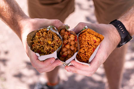Diverse tourist food. Tourist porridge in a retort package. Chickpea porridge. The tourist is holding various cereals. A variety of tourist cereals.