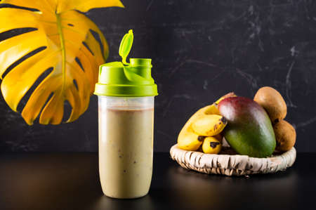 Fresh protein drink in a shaker. Protein drink with banana and fruit. Healthy food. Front view. Фото со стока