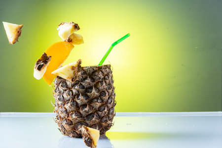 Flying pineapple slices. Pineapple slices in the air. Pineapple cocktail and flying slices. Green background.
