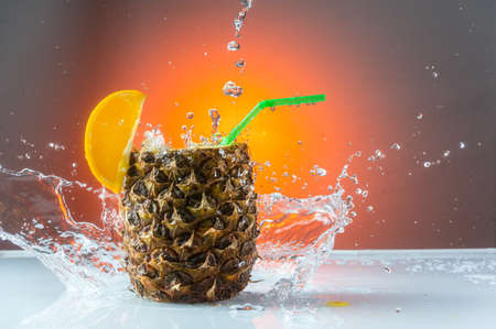 Splashing water around the pineapple. Pineapple cocktail and splash. Red background.