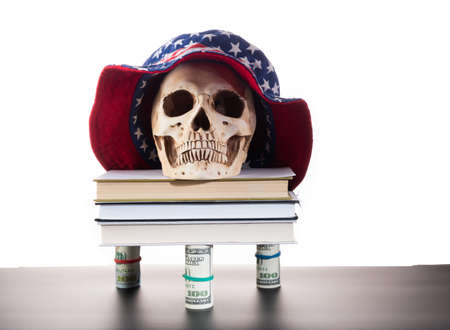 Human skull on books. Human skull in Panama. Books on money. Stand from rolls of dollars. Front view.