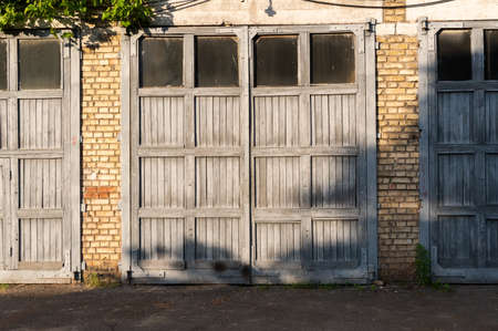 Large wooden gate to the building. Wooden gate to the garage. Gates for special equipment. Фото со стока