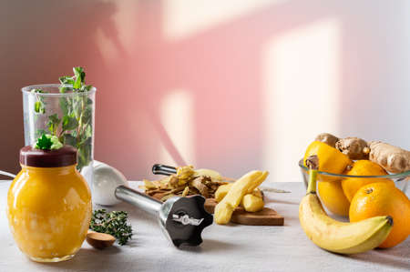 Peeled ginger root on the table. Fruit and honey on the table. Shadow from the window.