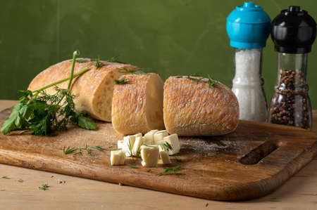 Freshly baked cheese roll. White roll and cheese diced. Salt and pepper in quilted flasks. Sliced bread on the board.