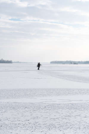 Lonely fisherman on ice. A lone fisherman in the middle of a large lake. Winter fishing. Vertical frame.