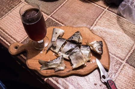 A glass of beer and sliced fish. Sliced dried fish on a wooden board. Drink beer at home.