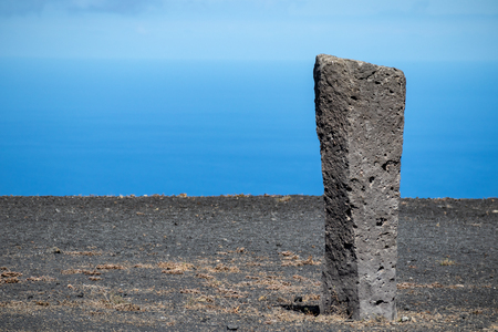 Processed stone column against the blue sky and ocean Banco de Imagens