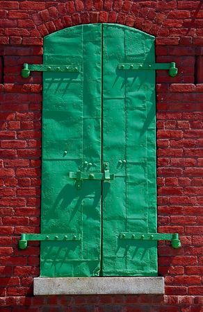 window with green shutter on historical building