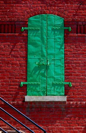 shutter: Green metal shutter and rail on brick building Stock Photo
