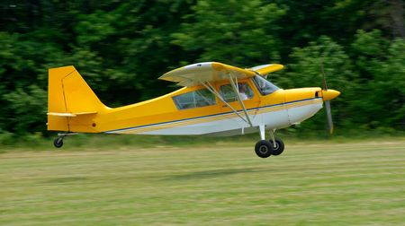 small aircraft landing on grass landing strip