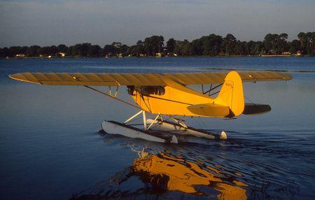 aero: yellow floatplane on lake Stock Photo