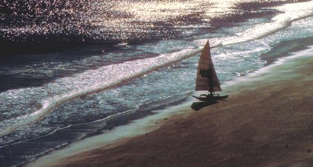 sailboat on the beach at sunset photo