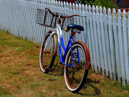 bicycle with basket and picket fence