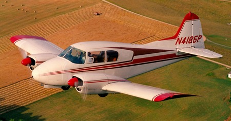 twin engine airplane over farmland