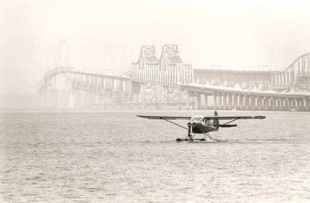 floatplane in fog with bridge in background in black and white