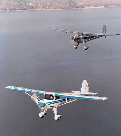 vintage light airplanes flying in formation over water