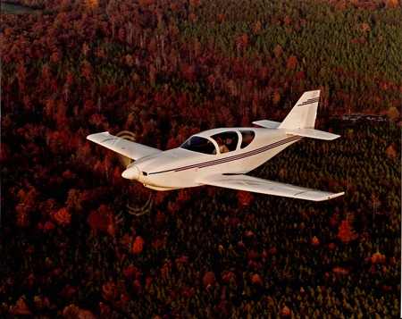 experimental airplane in flight over wooded area