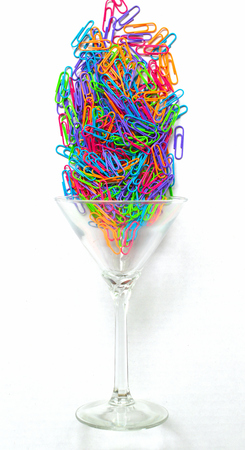 colorful paperclips falling into a glass