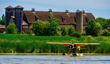 seaplane on a fiver with farm in background Stock Photo