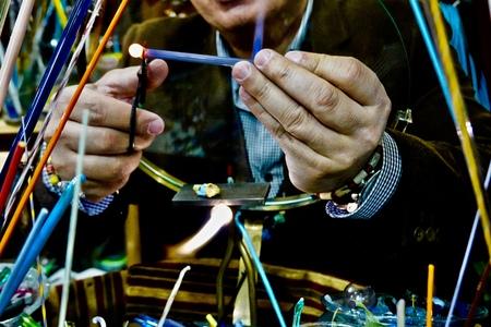 man making glass beads