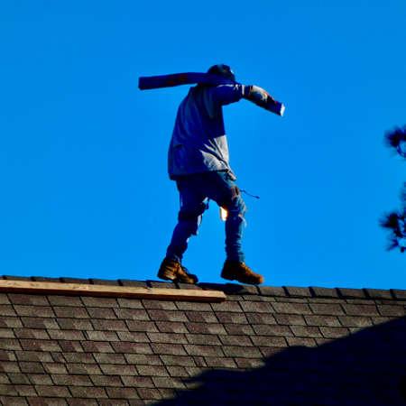 Workman carrying shingles on rooftop Zdjęcie Seryjne